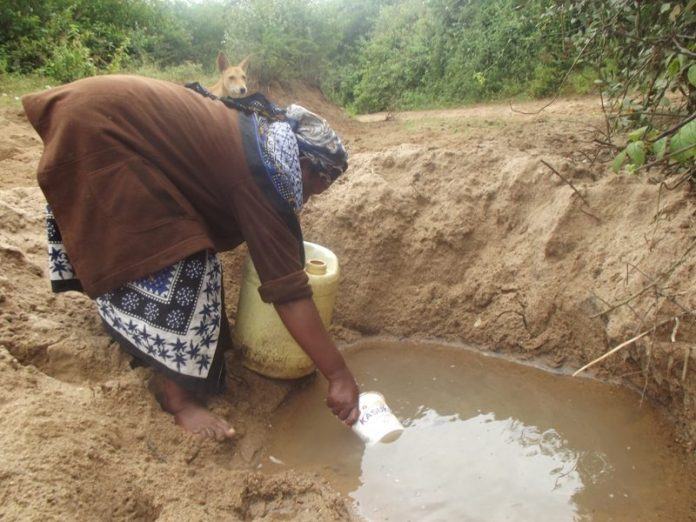 A woman fetches-water in scoophole in Kenya. Water problems in Africa continue to be a major issue.